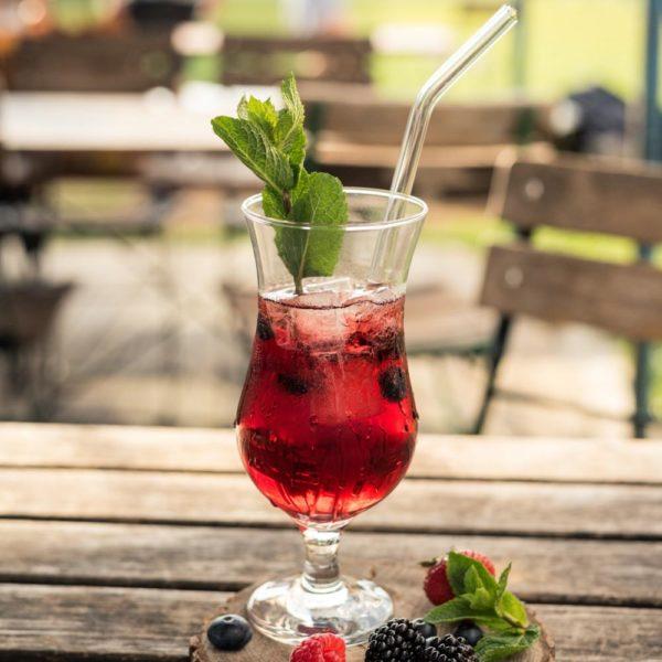 Gebogener Trinkhalm aus Glas in Cocktailglas (Hurricane Glas) gefüllt mit Cocktail, dekoriert mit Beeren und Minze