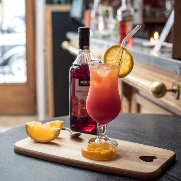 Wiederverwendbarer gebogener Trinkhalm aus Glas in Cocktail-Glas gefüllt mit Tequila Sunrise