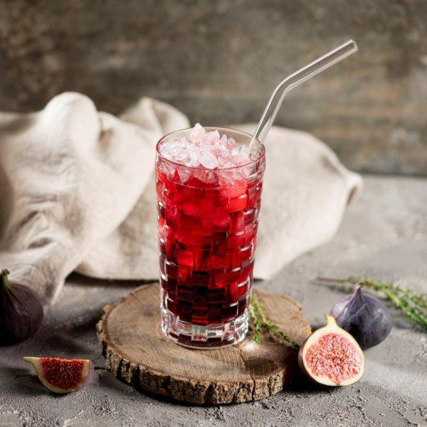 Gebogener Glastrinkhalm in Cocktailglas mit rotem Getränk auf Holz. Daneben Feigen und Thymian