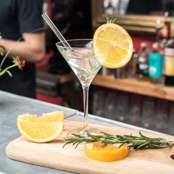 Glasstrohhalm in Martiniglas auf Bartresen mit Zitronen und Rosmarin