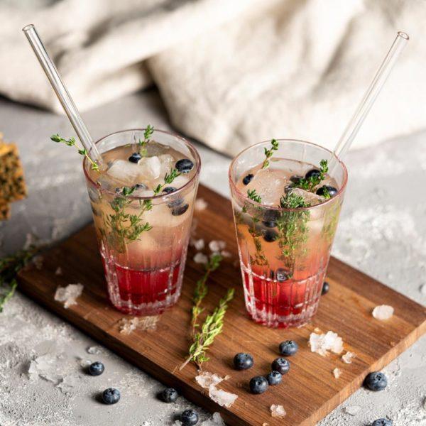 Cocktails mit wiederverwendbaren Glastrinkhalmen auf Holzbrett