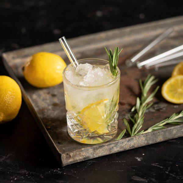 Kurzer Glastrinkhalm in Tumbler mit Gin, Zitrone und Rosmarin