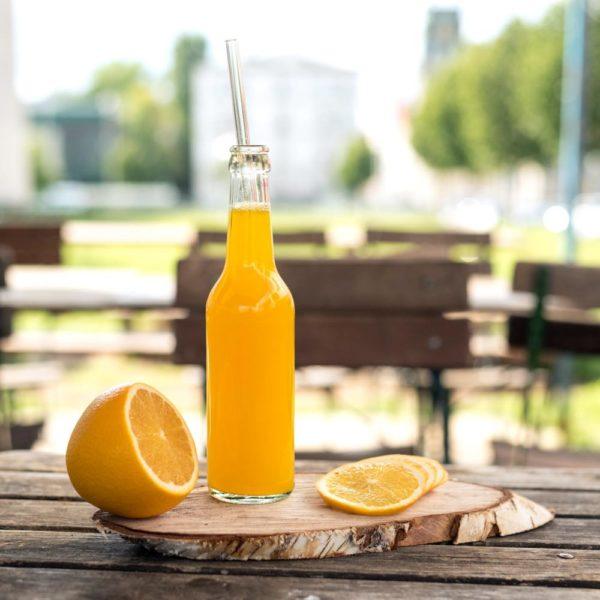 Wiederverwendbarer Trinkhalm 30 cm in Flasche mit Orangensaft