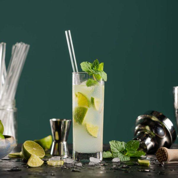 Glastrinkhalm in einem Cocktailglas mit Caipirinha. Im Hintergrund verschiedenes Bar-Equipment, Eiswürfel und Limetten