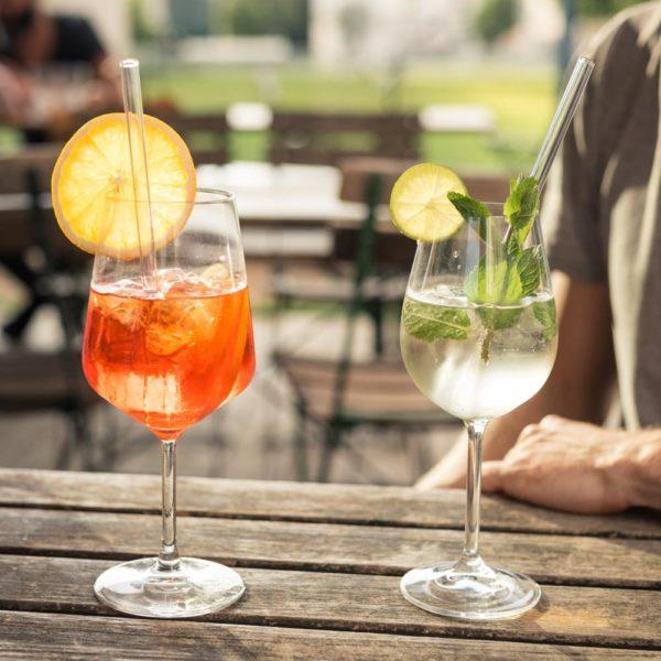 Glasstrohhalme in Weingläsern mit Aperol Spritz und Weinschorle auf Tisch