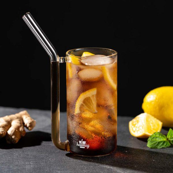 Trinkglas mit integriertem Halm, gefüllt mit Cola. Im Hintergrund Zitronen, Minze und Ingwer