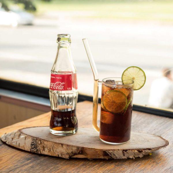 Handgemachtes Glas mit integriertem Trinkhalm gefüllt mit Cuba Libre, neben Cola Flasche